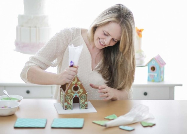 Catherine Beddall assembles a gingerbread house.