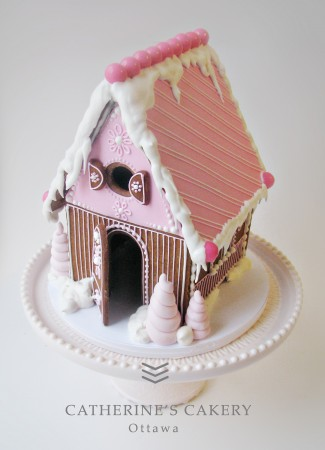 A pink gingerbread house sites on top of a cake tray.