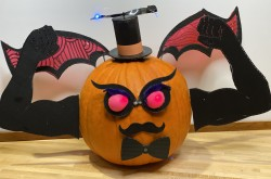 A pumpkin wearing a top hat, bow-tie, moustache, evil eyes, bat wings, and flexing two muscular arms.